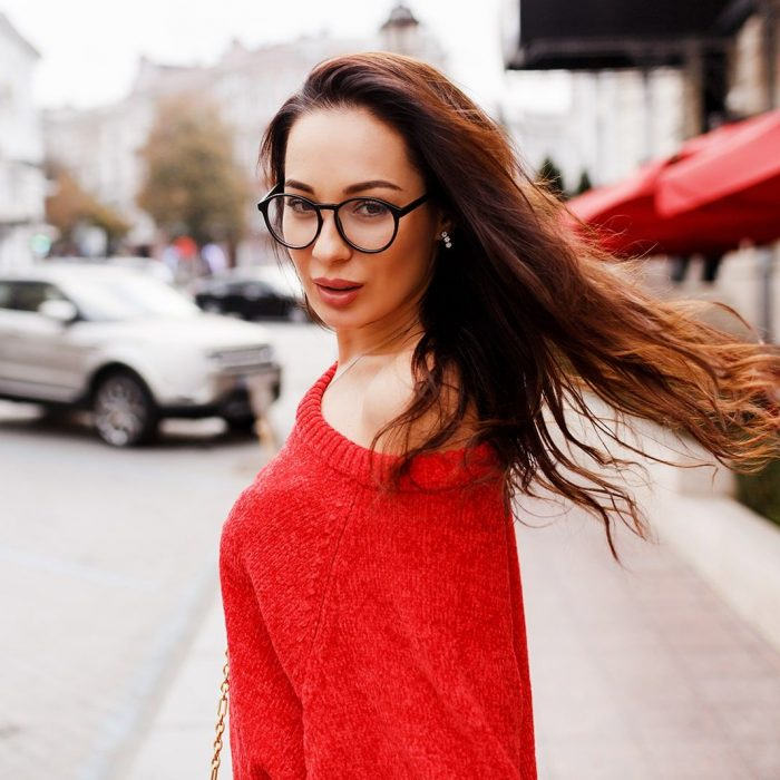 lifestyle-portrait-of-brunette-woman-with-long-hairs-in-red-cardigan-walking-through-street-windy-hairs-stylish-eyeglasses-min